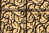 A detail view of a portion of a wrought iron gate on the grounds of Prague Castle. The repetitive nature of the shadows against a painted wall make this a nice background.