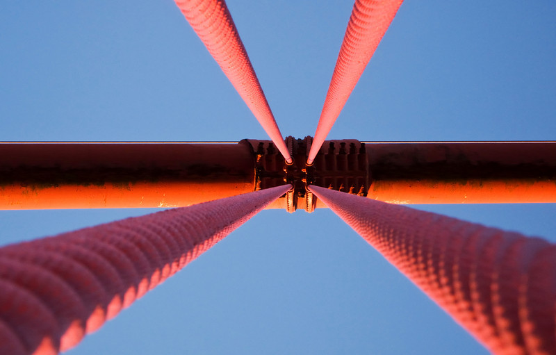 A view of the suspension cables on the Golden Gate Bridge in San Francisco. This perspective, looking upwards through the supporting cables, is an absract view.