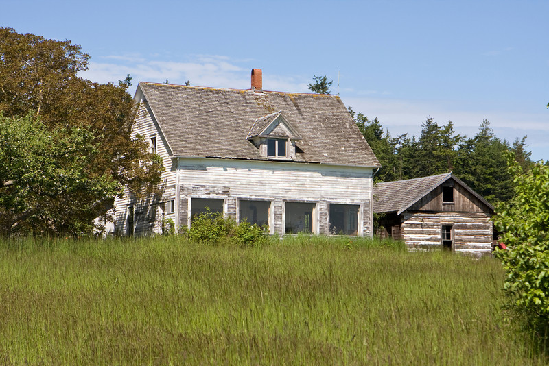 An old family farmhouse on Waldron Island, Washington viewed from across a grassy meadow. A barn stands to the right. Both of the wood buildings are very weathered.