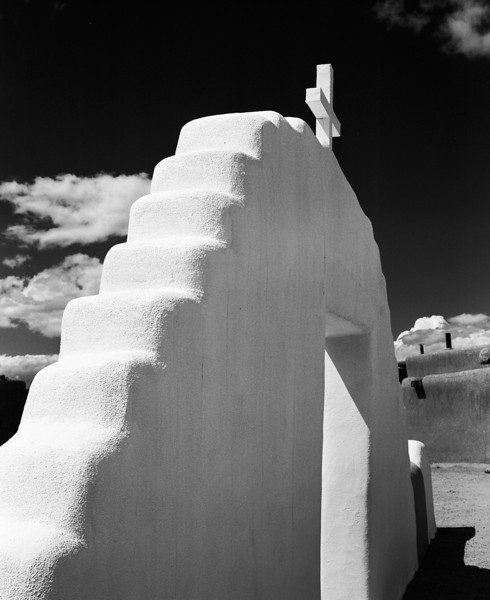 The adobe wall at the entrance to the San Geronimo Mission Church in New Mexico. The jagged wall looks like a set of steps rising towards the cross and the sky.