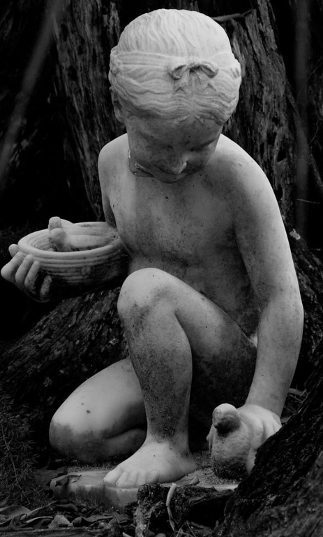 This lifelike statue sits between two trees in the shade. It's a great rendition of the peacefulness of being a child.