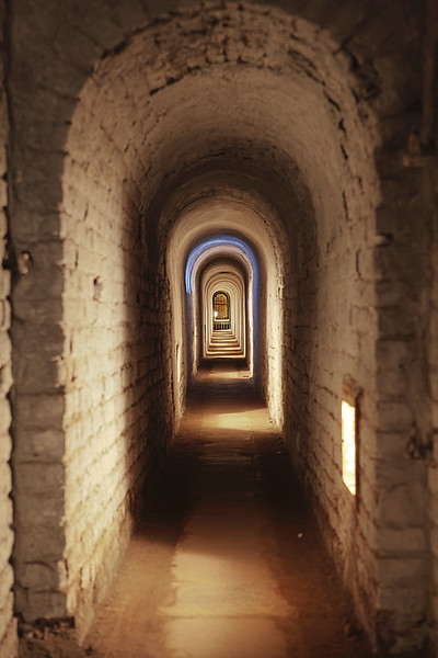 An underground corridor in the Little Fortress at Terezin in the Czech Republic. The alternating bands of light and dark depend on where lighting and external windows are located in the hallway.The Little Fortress was last used as a transit and prison camp by the Germans in World War II and is now a historic landmark.