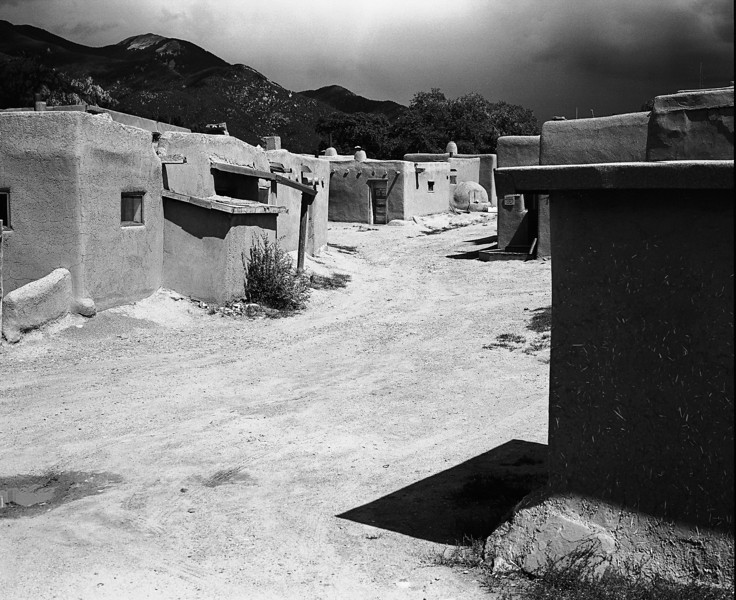 A view of one of the streets that meanders through the adobe buildings of the Taos Pueblo in New Mexico. A thunderstorm broods over the mountains.