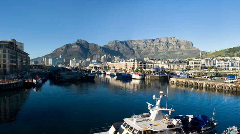 Panorama skyline view of Cape Town, South Africa with the harbor in the foreground and Table Mountain in the background.