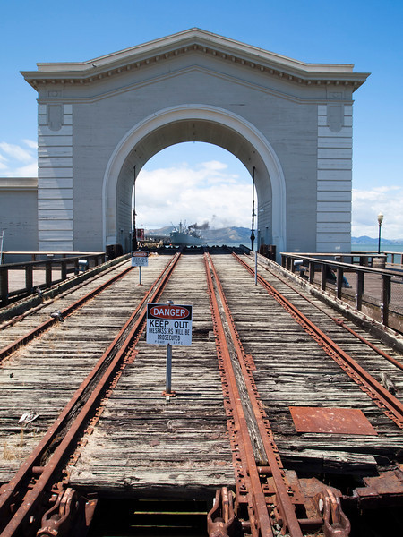 An unused boat launch and building with an arch on a San Francisco wharf. The railway tracks were used to run boats into the harbor.