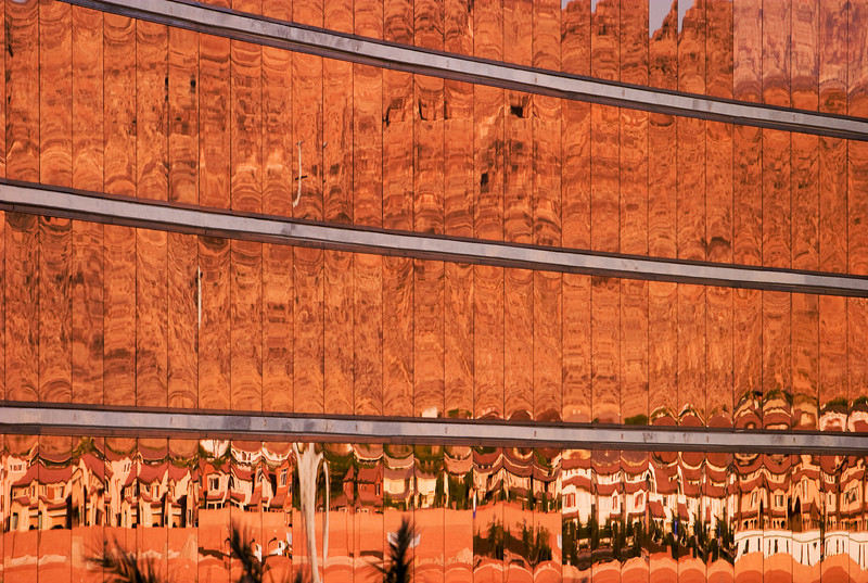 Gold-tinted windows on the facade of a hotel reflect a housing development and the red rocks of a mountain range in the background with a series of Dali-esque distortions.