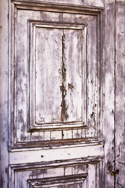 A detail view of an old, weather-beaten wood door with layers of peeling gray paint results in a distressed, weathered texture.