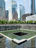 A view of the 9/11 memorial fountain and the surrounding buildings including the base of the new Freedom Tower building (replacing the World Trade Center) at the right.