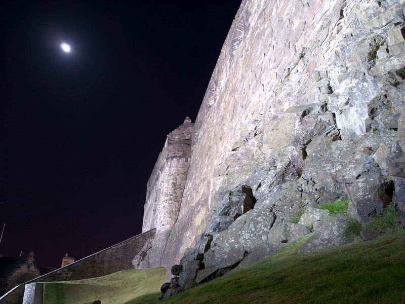 The exterior wall of Edinburgh Castle is built on a solid rock foundation. The fortifications of of heavy stones provide protection for the inner fortress. This long night exposure shows the moon with a bit of movement.
