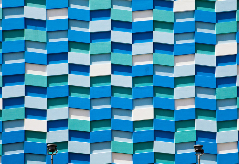 The exterior wall of an residential apartment tower is covered in an abstract pattern of rectangular shapes.