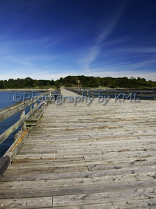 a long wood pier at the ocean