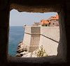 The fortress walls of Dubrovnik protected the old city on the Adriatic side. These stone walls are forty feet tall and up to 40 feet thick. At the edge, a lone turret provides protection for defenders.