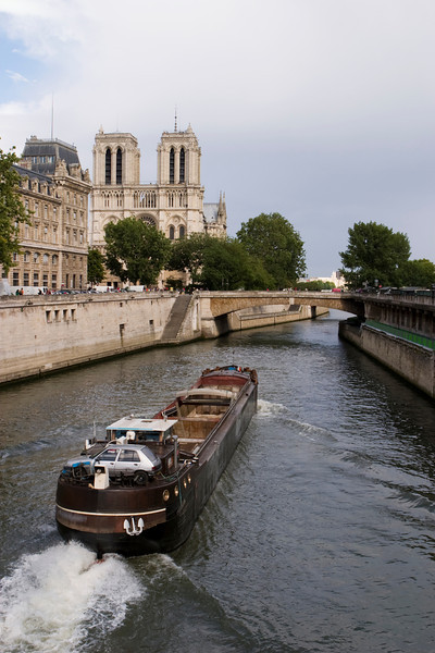 A French river boat moving downstream on the Seine River in the narrow river channel near Notre Dame and the Ile de France.