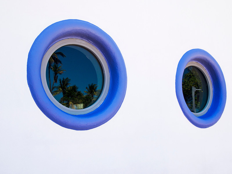 Two round windows painted in deep blue anchor an exterior wall on a building in South Beach in Miami. The reflection in the window shows the palm trees near the beach.