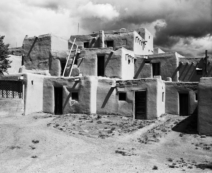 A traditional native American pueblo under storm clouds. The bulding is built with adobe mud walls, ladders, and typical square style for the rooms.