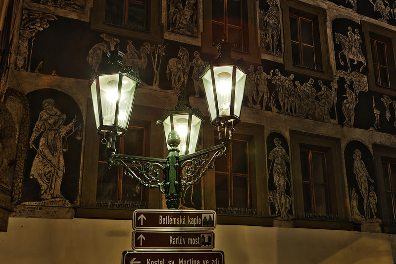 A traditional electric street lamp near the main square in Prague in the Czech Republic with an ornate painted building in the background.