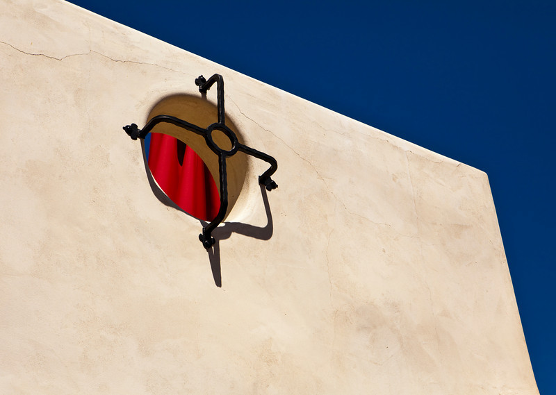 A simple architectural abstract based on the interplay between a white stucco wall with a few cracks, a deep blue sky, and a bright red umbrella.