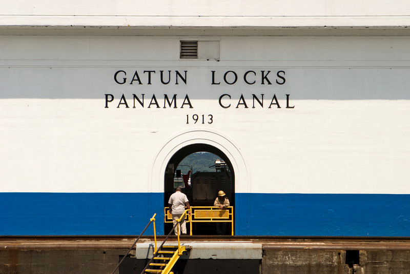 The central building at the Gatun Locks on the Panama Canal. The door provides a portal to view some of the equipment and the mountains in the background.