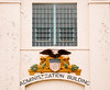 "A bald eagle emblem centered below a window at a prison administration building. The word ""FREE"" on the flag is an ironic symbol for a penitentiary."