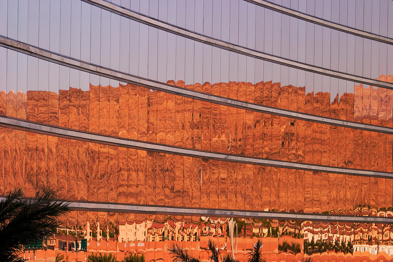 Gold-tinted windows on the facade of a hotel reflect the peaks of a nearby mountain range looming over a housing development with a series of Dali-esque reflections.