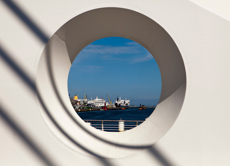 A view of ships in at the docks in the harbor in Dublin, Ireland through a porthole-like circle in the Samuel Beckett Bridge.