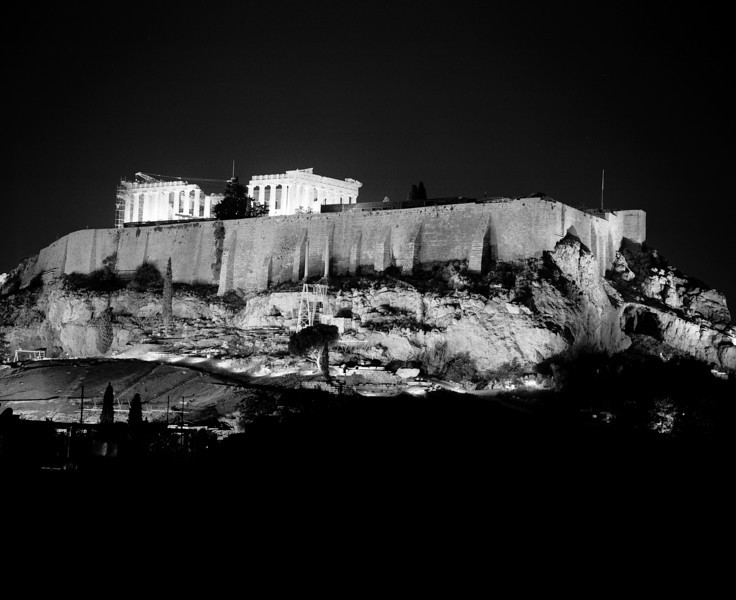 A view of the Acropolis in Athens at midnight. The hilltop and the Acropolis are brightly illuminated.