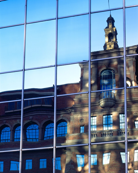 The old and the new.  The old bank building is reflected in the mirrored surface of the new bank building.