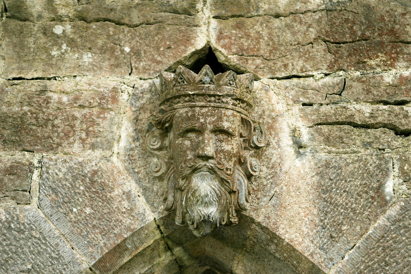 An old stone detail from a gate in Cong, Ireland shows what appears to be a king with a crown. This old sculptural element is heavily weathered and chipped with a bit of moss and lichen discoloring the stone.
