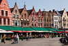 Restaurants and shops line the edges of Market Square in Bruges, Belgium with classic building shapes and rooflines.