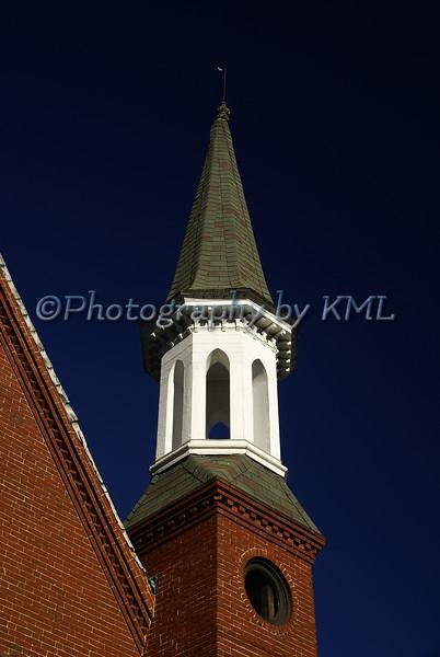 a brick church and steeple against a blue sky