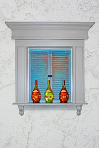 shuttered window with wine bottles