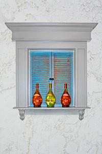 shuttered window with wine bottles