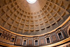 A large beam of light coming from the oculus illuminates the ceiling pattern of the Pantheon in Rome.