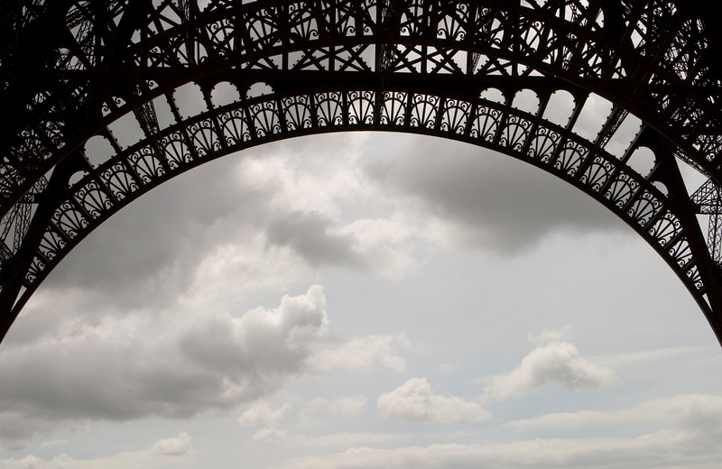 A detailed view of the ironwork on the main arches of the Eiffel Tower.