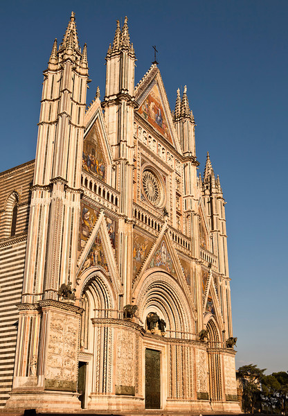 The front facade of the Orvieto Cathedral is ornate and detailed with colorful mosaics, intricate carvings, bronze statues, bell towers and more. It is a magnificent example of 14th century Italian architecture that evolved from Romanesque to Gothic.