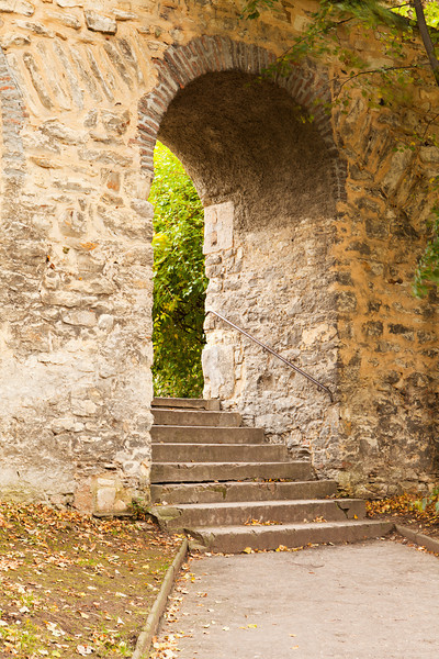 A stone arch provides a passageway through an old stone wall in the park on Petrin Hill in Prague. A peaceful scene in a quiet part of the city.