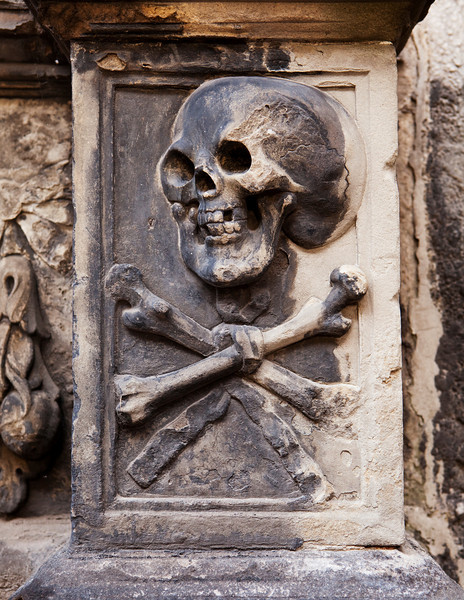 A grisly image of death grimacing with a skull and crossbones on a headstone in Kylemore Abbey in Edinburgh, Scotland.