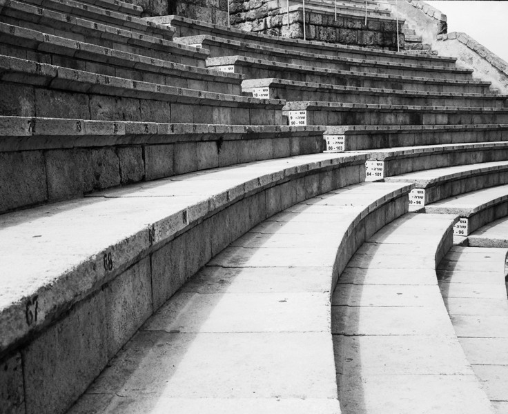 The seats curve around in an arc around the stage of the restored ruins of the Roman theatre at Caesaria in Israel. (Scanned from black and white film.)