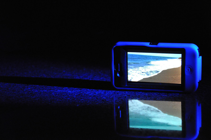 Experimenting with high contrast images, I came up with this idea. I backlit the blue Iphone cover with a blue LED light & played a video I took at the ocean earlier that day. The kitchen counter provided the perfect reflective surface. <br /> Low light images often require several takes to finally have a good image, but it's a lot of fun to pull it all together.