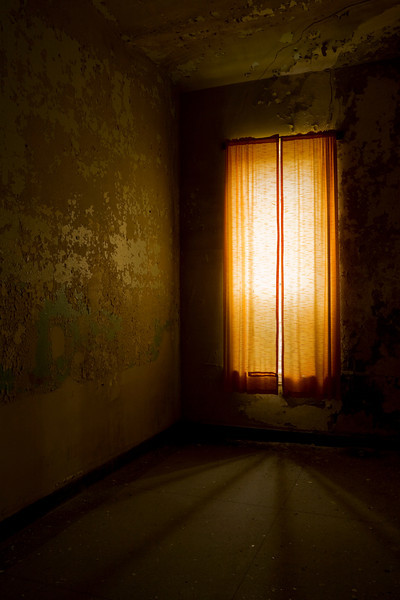"Dim light shining through a red curtain over a giant window in a 14"" tall patient bedroom, Athens State Hospital."