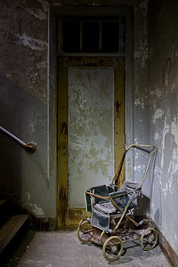 Pram sitting at the bottom of a staircase in the wards at Worcester State Hospital.  This site has since been demolished.