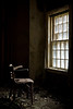 Brown chair near a window in the 1854 Kirkbride building, Taunton State Hospital.  This site has since been demolished.