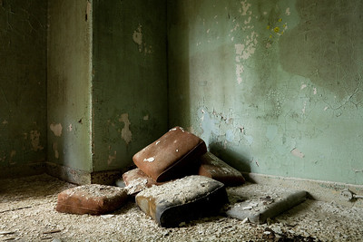Couch cushions piled in corner of patient room, Taunton State Hospital.