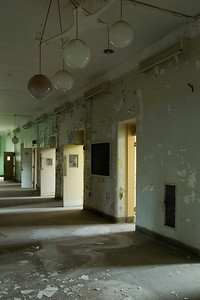 "Seclusion rooms in a hallway with globe lights, one of which is filled with dirty water.  Kirkbride building (""Old Main""), Athens State Hospital."