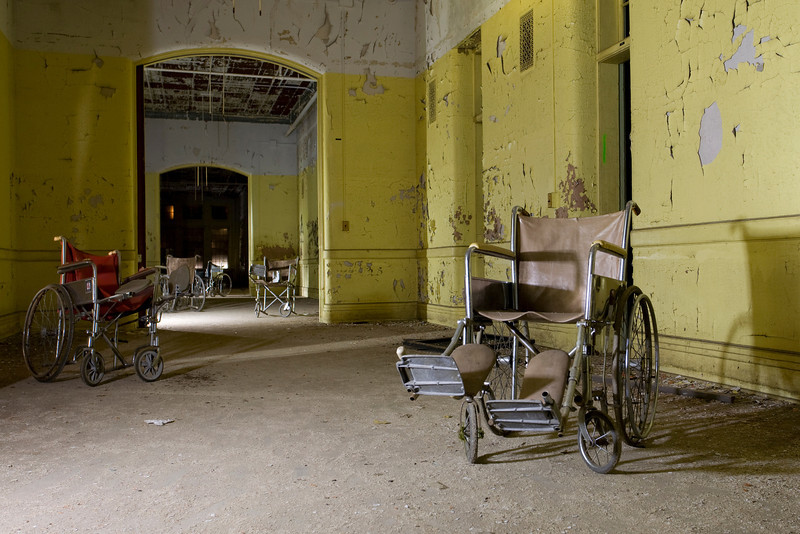 Wheelchairs left on a darkened ward in the innermost brick ward at Buffalo State Hospital.