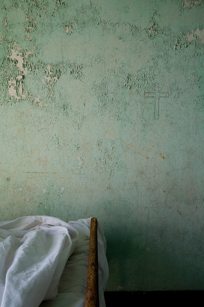 Simple cross penciled onto wall above bed in patient bedroom, Kirkbride Building, Taunton State Hospital.