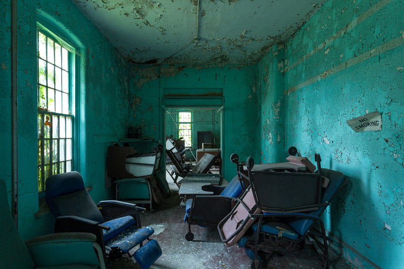 Geriatric chairs piled up in the Maples Building at Willard State Hospital, New York's long-term-care asylum.  Many elderly patients would live out their final days in buildings such as this one, which was constructed in 1872.
