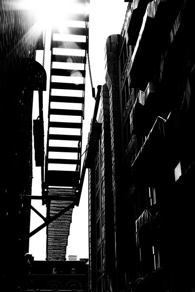 Grunge stairway in a narrow alley. Black and white.