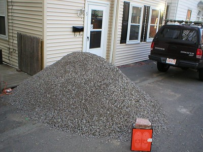 with the hole dug, time to fill the hole.  The first layer was 4 cubic yards of stone pack.  Too bad it could only be dumped in the street.