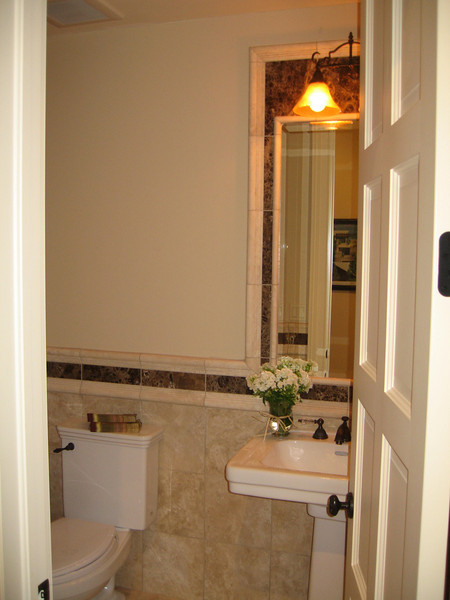 Matching oil rubbed bronze hardware on the door, the toilet and the sink, tie in with the dark marble tile inlay at the wainscot and around the mirror.  Simple elegance for a powder bath.
